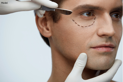 A man receiving a consultation for his eyelid lift that will help restore his youthfulness by removing facial sagging and wrinkles.