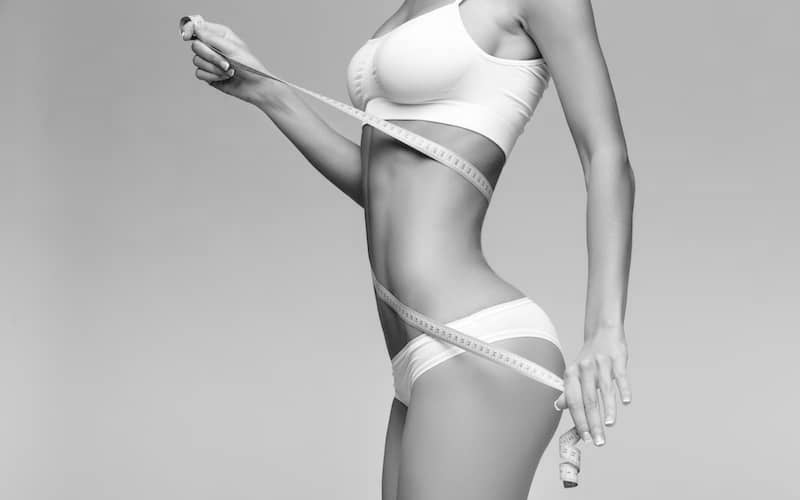 Slim torso of a woman in bra and panties, holding a tape measure wrapped around stomach after liposuction