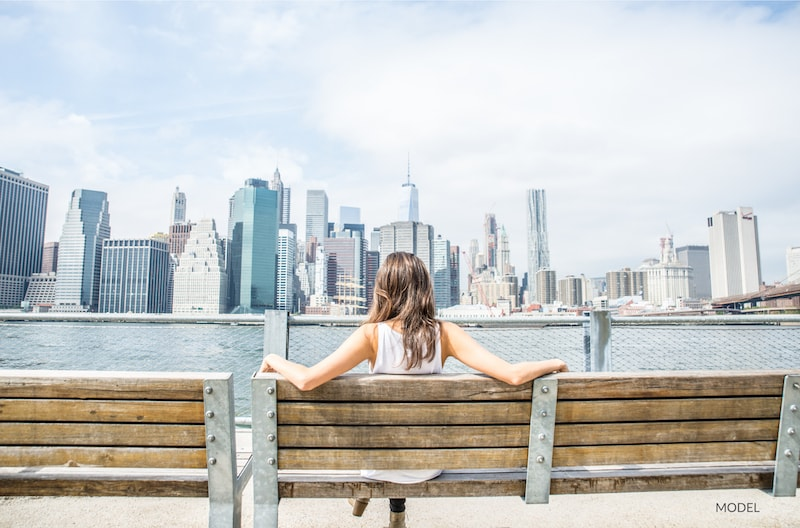 Woman sitting on a wooden bench looking out at the New York City skyline.