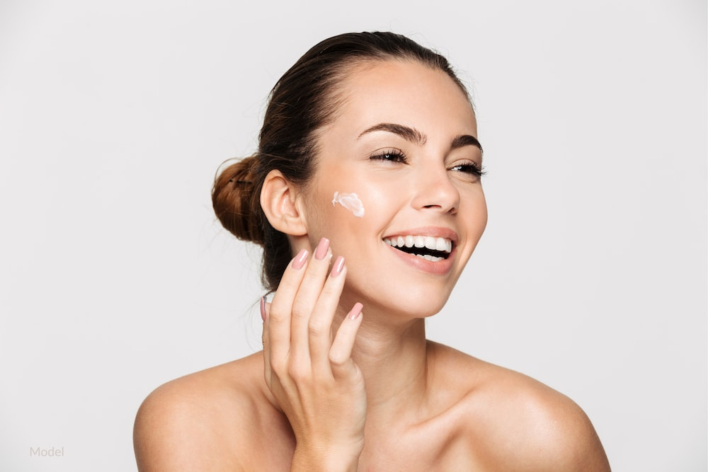 Happy woman applying skincare properly to maintain good skin health.