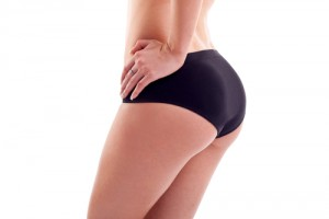 Girl from the waist down in black underwear with a large buttocks on a white backfround