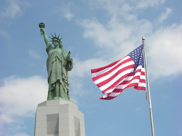 American flag next to the Statue of Liberty