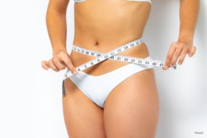 Woman wrapping a tape measure around her narrow waist to show the concept of weight loss or tummy tuck surgery.