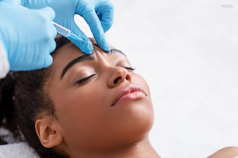 African American woman getting BOTOX Cosmetic injection in her forehead.