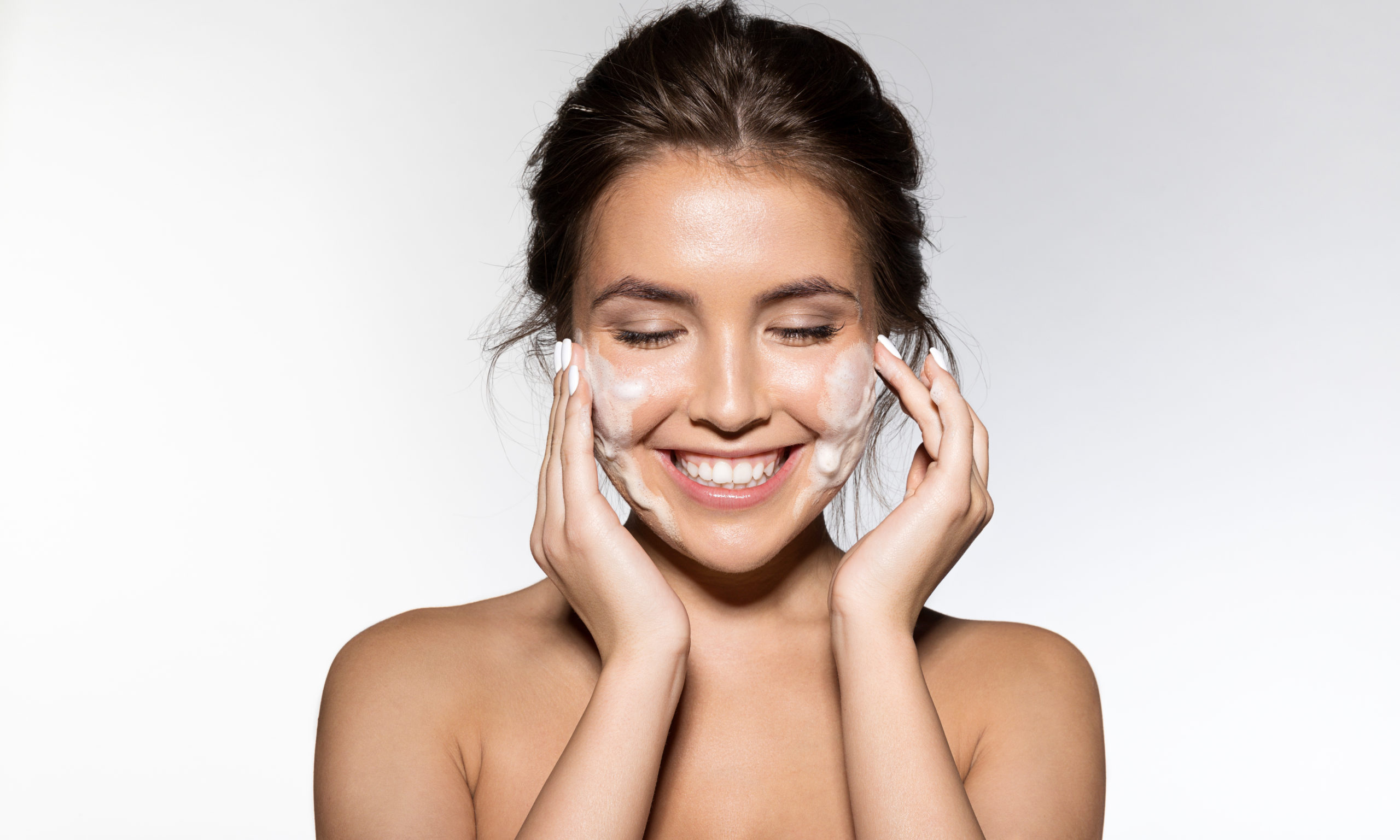 Woman rubbing lotion on her face